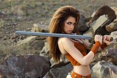 Het mooie meisje met een zwaard in een kostuum stock afbeelding