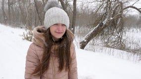 Het mooie meisje met fladderend haar glimlacht terwijl het lopen in park in een blizzard in de winter Langzame Motie stock video