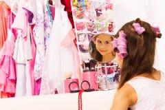 Het mooie meisje met haar-krulspelden kijkt in spiegel Royalty-vrije Stock Afbeelding
