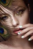 Het mooie meisje met heldere make-up, het manicureontwerp en de pauw bevederen op haar gezicht Kunstspijkers stock afbeelding
