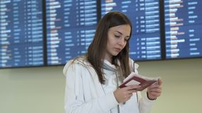 Het mooie meisje met kaartje en paspoort in haar handen controleert tijd van vertrek met informatieraad bij luchthaven stock video