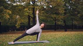 Het mooie meisje met kort krullend haar doet yoga die zich in openlucht in Strijder bevinden stelt zich dan het uitrekken lichaam stock video