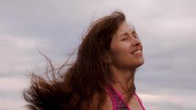 Het mooie meisje met lang die haar door wind wordt verfomfaaid verheugt zich in regen en glimlacht Vrouwengangen in bewolkt weer  stock video