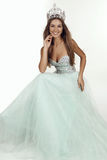 Het mooie meisje met lang haar draagt luxueuze kleding en kroon Royalty-vrije Stock Foto