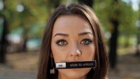 Het mooie meisje met lang haar en leuke ogen bekijkt camera met naambord op mond stock footage