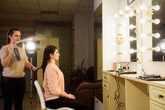Het mooie meisje met lang haar, kapper weeft een Franse vlecht, in een schoonheidssalon Het professionele haarverzorging en creër royalty-vrije stock afbeeldingen