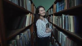Het mooie meisje met lang zwart haar gaat tussen de planken in de bibliotheek stock footage