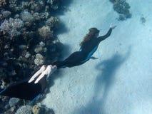 Het mooie meisje met monofin zwemt dichtbij koraalrif Royalty-vrije Stock Foto