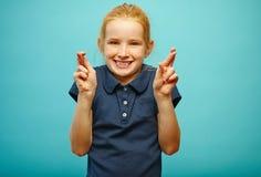 Het mooie meisje met rode haar en sproeten maakt een wens, gekruiste vingers, gelooft in vervulling van dromen, heeft a stock afbeeldingen