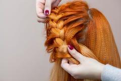 Het mooie meisje met rood haar, kapper weeft een vlechtclose-up, in een schoonheidssalon stock foto's