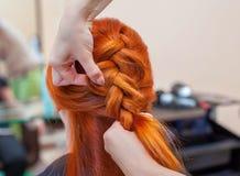 Het mooie meisje met rood haar, kapper weeft een vlechtclose-up, in een schoonheidssalon stock foto