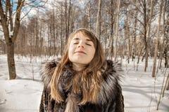 Het mooie meisje met sneeuwvlokken in haar haar geniet van aard op een Zonnige de winterdag royalty-vrije stock foto's