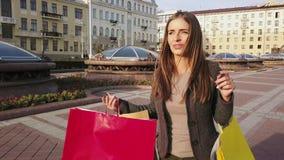 Het mooie meisje met steunen op haar tanden met het winkelen doet het lopen in een stad in zakken stock footage