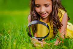 Het mooie meisje met vergrootglas bekijkt gras Stock Foto's