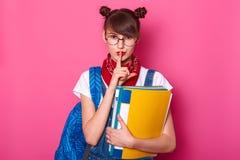 Het mooie meisje met vinger op lippen kent zeer machteloos geheim Het schoolmeisje met bossen op hoofd, met rode bandana op hals, royalty-vrije stock foto's