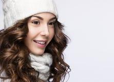 Het mooie meisje met zachte make-up, de krullen en de glimlach in wit breien hoed Warm de winterbeeld Het Gezicht van de schoonhe Royalty-vrije Stock Foto