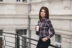 Het mooie meisje, mooi brunette met elegant kapsel in een plaidoverhemd drinkt kop in openlucht van koffie in de zomerkoffie Stock Fotografie