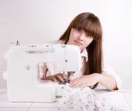 Het mooie meisje naaien Stock Afbeeldingen