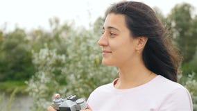 Het mooie meisje neemt beelden op de retro camera Langzame Motie Close-up stock video
