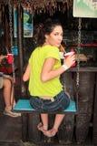 Het mooie meisje neemt een verfrissing in een Caraïbische strandbar sitt stock foto