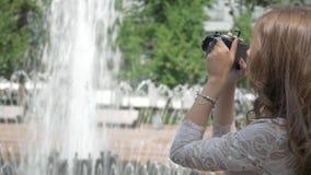 Het mooie meisje neemt foto's van een stadsfontein, op een uitstekende camera stock video