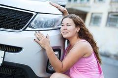 Het mooie meisje omhelst voertuig Stock Foto's