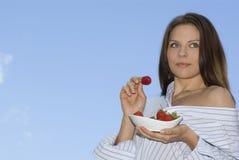 Het mooie meisje ontspannen op balkon en eet rode vers Stock Afbeelding