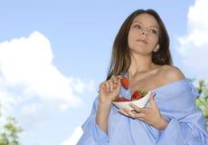 Het mooie meisje ontspannen op balkon en eet rode vers Royalty-vrije Stock Afbeelding
