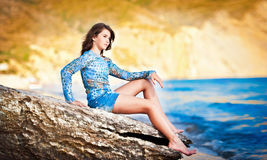 Het mooie meisje ontspannen op de rots dichtbij het overzees Royalty-vrije Stock Afbeelding