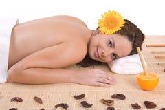 Het mooie meisje ontspannen op massagelijst Stock Foto