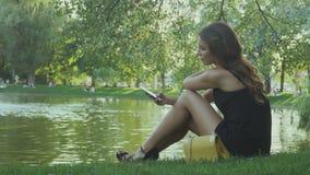 Het mooie meisje ontspant dichtbij de rivier op groene gras en gebruikssmartphone stock footage