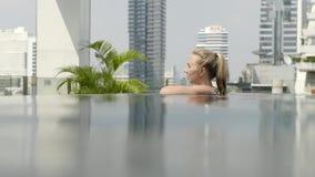 Het mooie meisje ontspant in een oneindigheidspool stock videobeelden