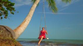 Het mooie meisje ontspant op de schommeling bij het strand De vrouw op de oceaankust het tropische eiland in Vietnam stock footage