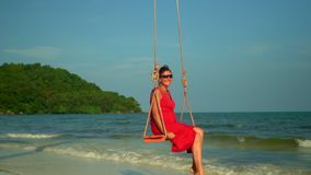 Het mooie meisje ontspant op de schommeling bij het strand De vrouw zit op een schommeling op de bank van het eiland Mening van e stock video
