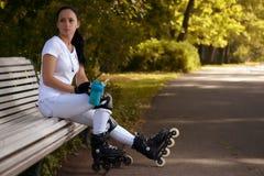 Het mooie meisje op rolschaatsen in park zit op bank en drinkt water Stock Foto's
