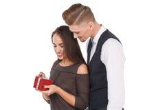 Het mooie meisje pakt een giftdoos uit, let de kerel op deze status achter het meisje De dag van de valentijnskaart `s Geïsoleerd stock fotografie