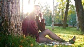Het mooie meisje in park zit op algemeen en het spreken op haar telefoon stock videobeelden