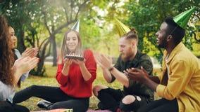 Het mooie meisje in partijhoed viert verjaardag met vrienden in park op picknick die wens maken, blazend kaarsen op cake stock videobeelden
