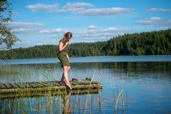 Het mooie meisje raakt het water stock fotografie
