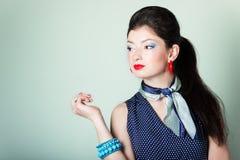 Het mooie meisje in retro stijl met een blauw kostuum met een heldere mooie make-up met rode lippen is in de Studio op een blauwe Stock Afbeelding