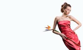 Het mooie meisje in rode kleding houdt exotische bloem Royalty-vrije Stock Afbeeldingen