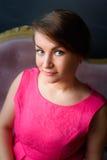 Het mooie meisje in roze bekijkt de camera Royalty-vrije Stock Afbeeldingen