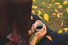 Het mooie meisje rusten en het drinken koffiezitting in de herfsttuin Stock Foto's