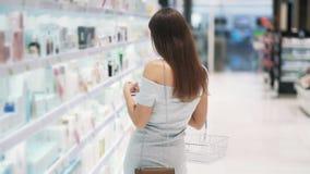 Het mooie meisje in schoonheidsmiddelenwinkel kiest gezichtsroom, zet het in mand, langzame motie stock videobeelden