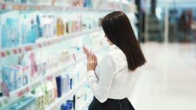 Het mooie meisje in schoonheidsmiddelenwinkel kiest room, bekijkt goederen, langzame motie stock video