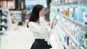 Het mooie meisje in schoonheidsmiddelenwinkel kiest room, bekijkt goederen, leest ingrediënten stock video