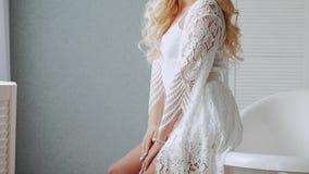 Het mooie meisje in schuimend zit op de rand van een witte badkuip stock videobeelden