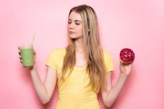 Het mooie meisje selecteert tussen gezonde groene gluten-vrije organische smoothie en ongezond voedsel Het concept van de voeding royalty-vrije stock foto