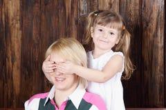 Het mooie meisje sluit ogen aan moeder. Stock Afbeeldingen
