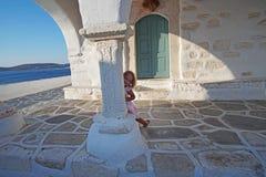 Het mooie meisje spelen in de binnenplaats van de kerk van Agios Konstantinou, een traditionele Cycladic-kerk met een blauwe koep stock foto's